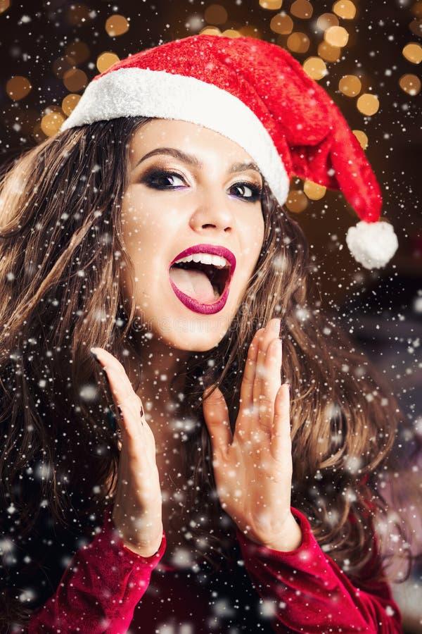 Ragazza in cappello di Santa e vestire posa mentre neve che cade intorno immagine stock