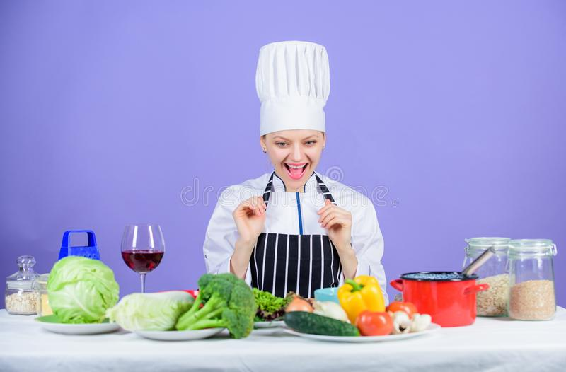 Ragazza in cappello ed in grembiule Cottura dell'alimento sano Ingredienti degli ortaggi freschi per la cottura del pasto Lascia  immagini stock