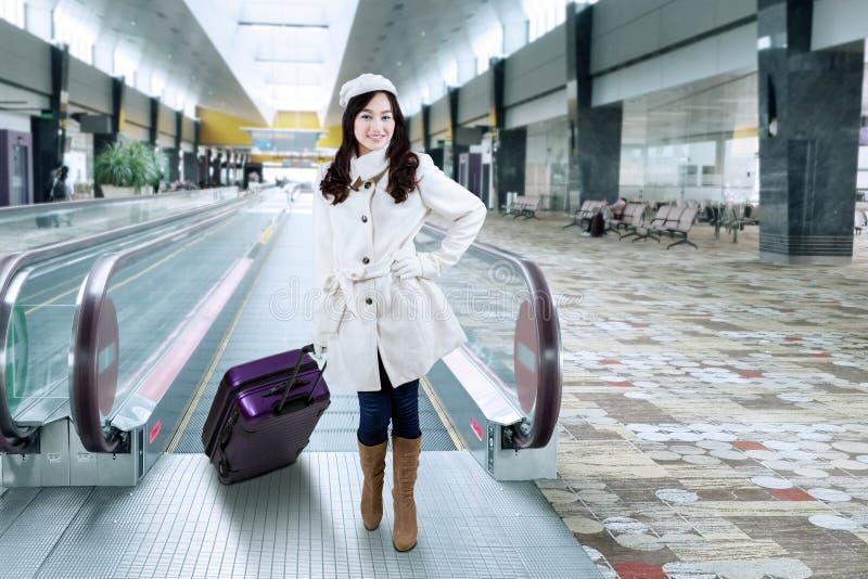 Ragazza in cappotto di inverno al corridoio dell'aeroporto fotografie stock libere da diritti