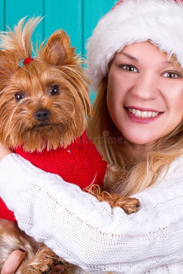 Ragazza in cappuccio di Santa con il cane del yorkie in maglione rosso immagine stock libera da diritti