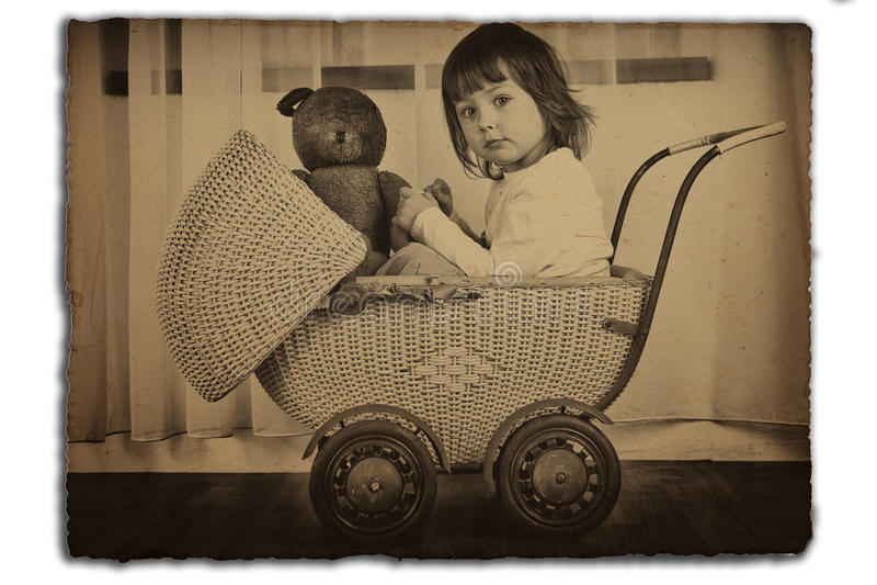 Ragazza in carrello di bambino antico immagini stock libere da diritti