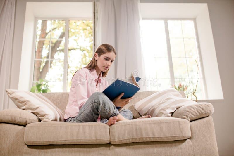 Ragazza a casa che si siede sulla rivista della lettura dello strato immagini stock