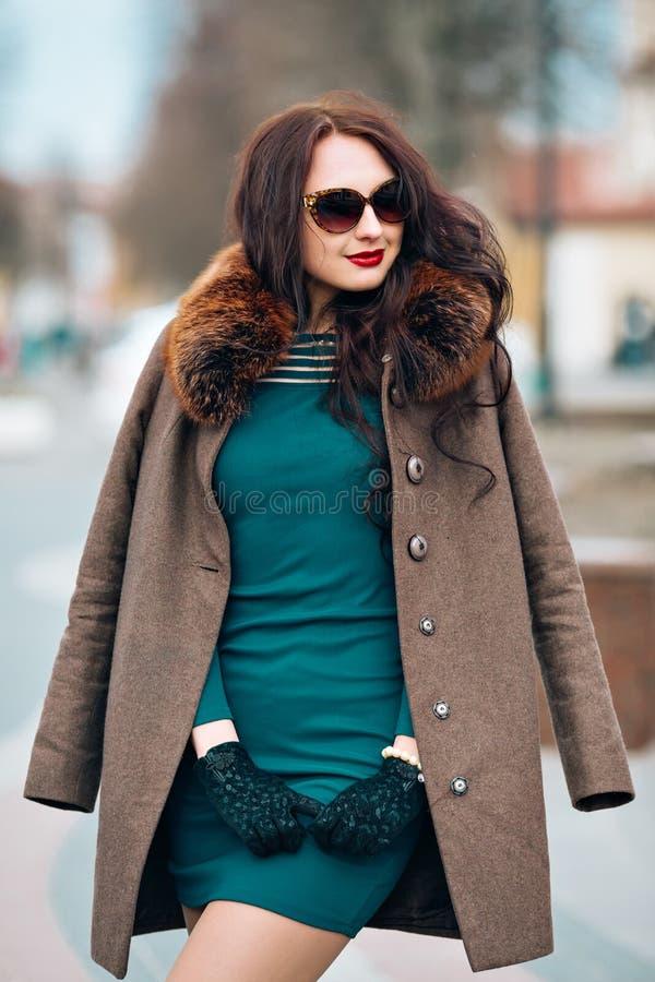 Ragazza castana affascinante sexy, bella giovane donna con capelli scuri lunghi eleganti, occhiali da sole alla moda d'uso, verde immagini stock