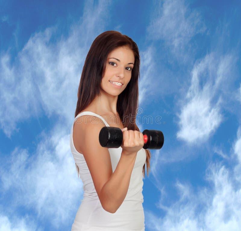 Ragazza castana attraente che stringe i loro muscoli fotografie stock