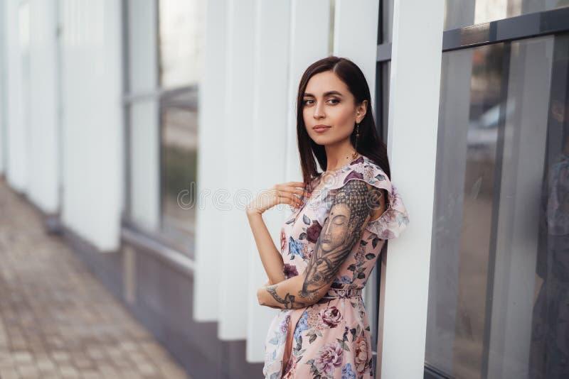 Ragazza castana attraente a colori vestito che posa vicino al centro di affari fotografie stock