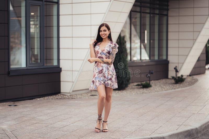 Ragazza castana attraente a colori vestito che posa vicino al centro di affari fotografia stock