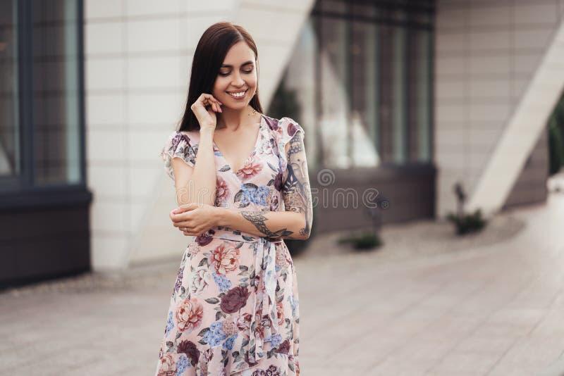 Ragazza castana attraente a colori vestito che posa vicino alla costruzione moderna fotografia stock