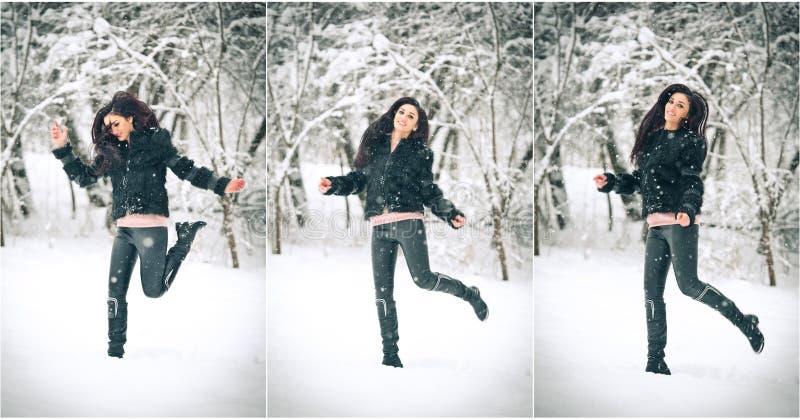 Ragazza castana attraente nel nero che posa gioco nel paesaggio di inverno Bella giovane donna con capelli lunghi che gode della  fotografia stock libera da diritti