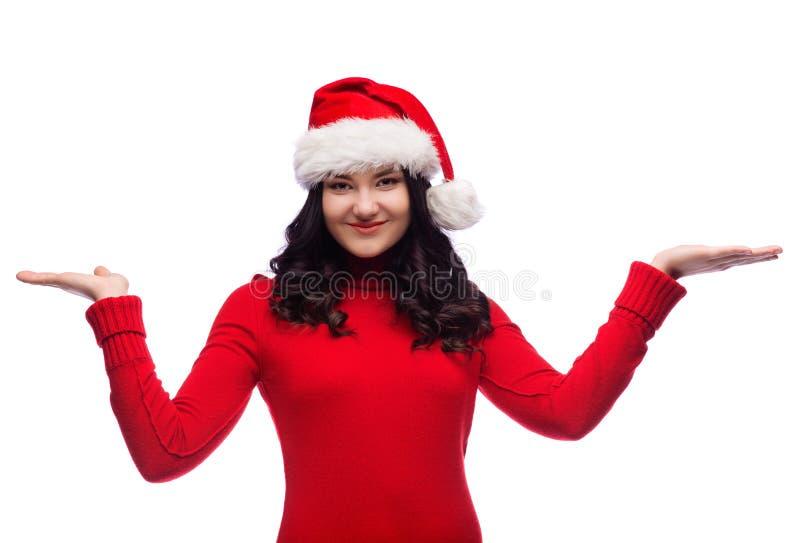 Ragazza castana che porta il cappello di Santa che presenta qualcosa sulle palme Isolato immagine stock