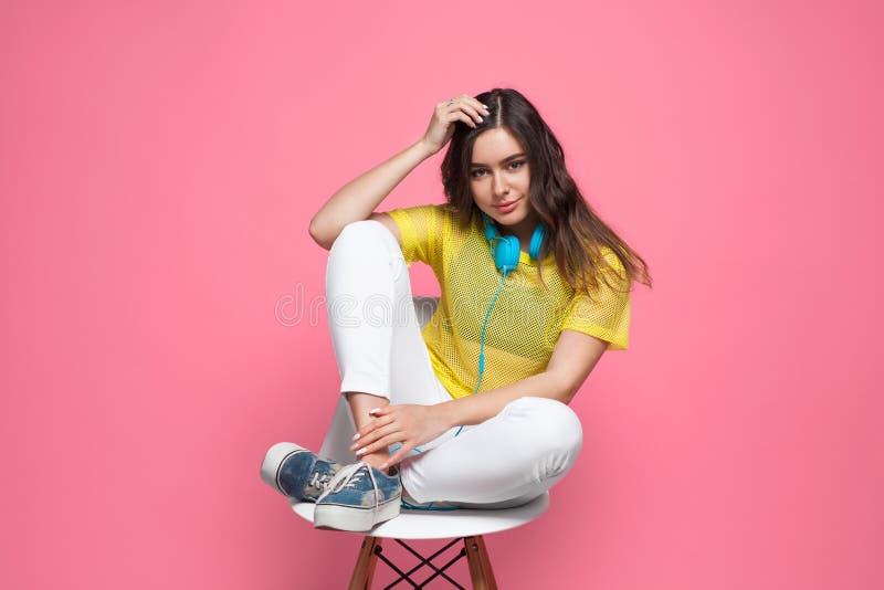 Ragazza castana che si siede in testa commovente della sedia fotografia stock libera da diritti