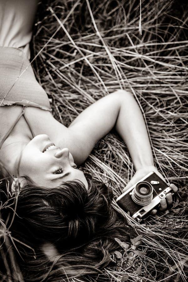 Ragazza castana che si trova all'erba con la macchina fotografica nell'ora legale fotografia stock libera da diritti