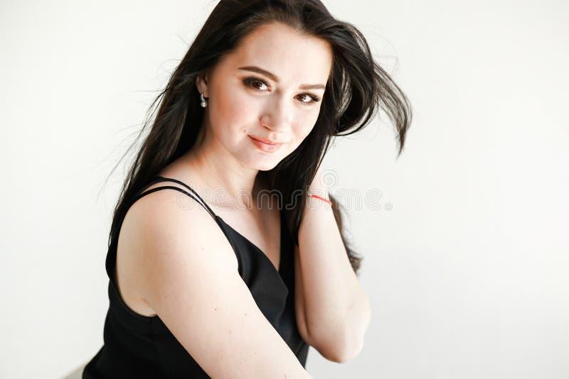 Ragazza castana con capelli lunghi e brillanti Bello modello sullo spazio bianco della copia del fondo immagini stock