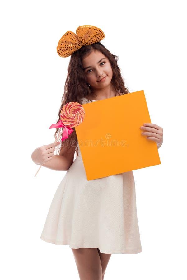 Ragazza castana con capelli lunghi in un vestito bianco con un arco sulla sua testa con la caramella e un foglio di carta nelle m fotografia stock
