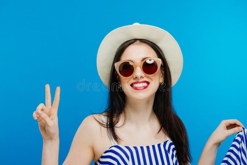 Ragazza castana con gli occhiali da sole ed il cappello su fondo blu fotografia stock