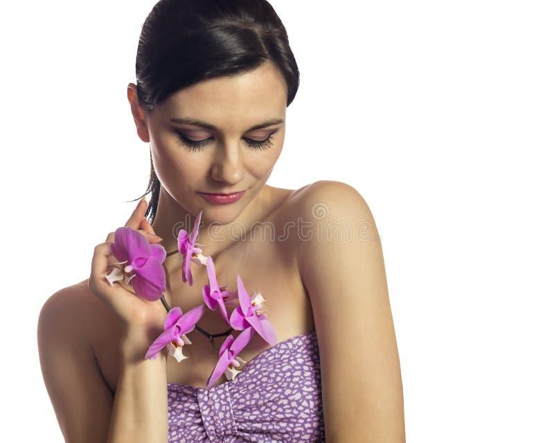 Ragazza castana con i fiori dell'orchidea Isolato immagine stock libera da diritti