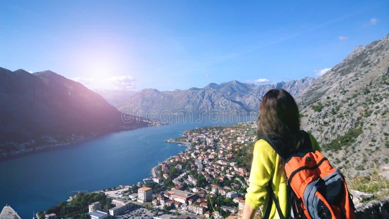 Ragazza castana con uno zaino arancio che gode della vista della baia di Boka nel Montenegro La vista dalla parte posteriore immagine stock