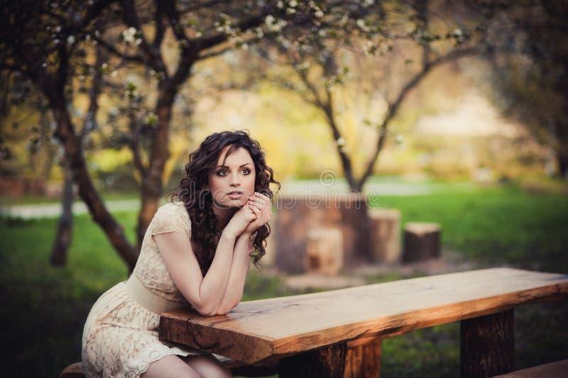 Ragazza castana dagli occhi castani che si siede su un banco fotografia stock