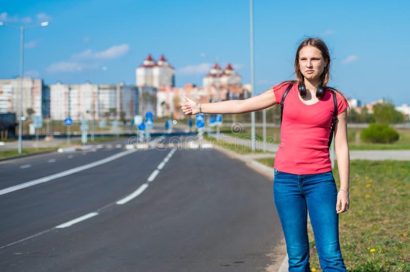 Ragazza castana dell'adolescente in maglietta di corallo con capelli lunghi che fa auto-stop dal bordo della strada Sfogliare un  fotografia stock