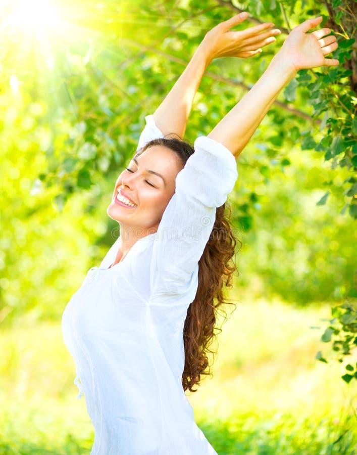 Ragazza castana felice e sorridente con il sorriso sano che si rilassa nel parco di estate immagini stock