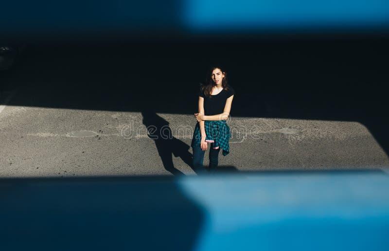 Ragazza castana nello stile del nero della roccia, stante all'aperto nella via della città fotografia stock