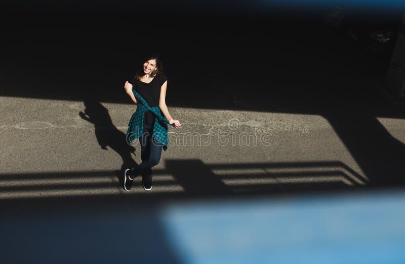 Ragazza castana nello stile del nero della roccia, stante all'aperto nella via della città fotografie stock libere da diritti