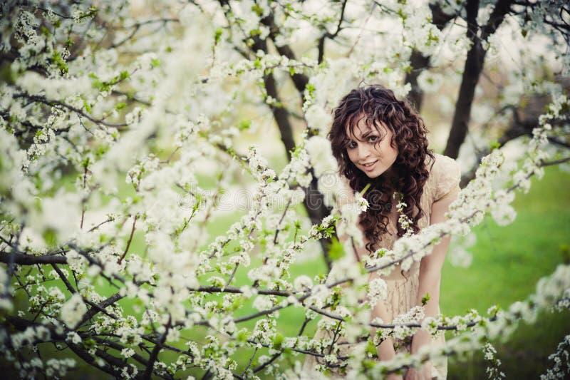 Ragazza castana riccia che sta negli alberi sboccianti immagini stock libere da diritti