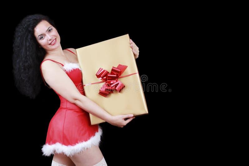 Ragazza castana sensuale di Natale con un grande contenitore di regalo, isolato sul nero fotografia stock libera da diritti