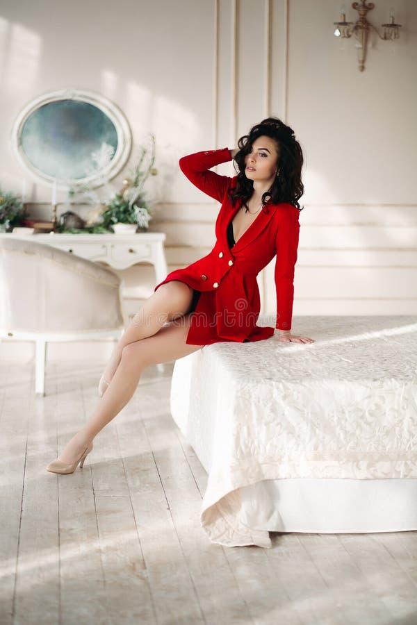 Ragazza castana sexy nella posa seducente della giacca sportiva rossa al letto fotografie stock libere da diritti
