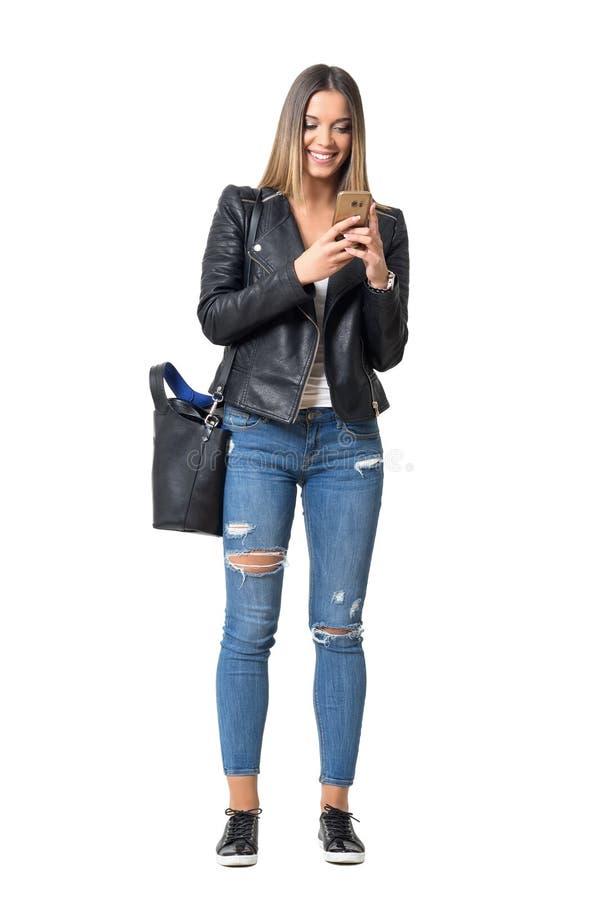 Ragazza casuale sorridente felice di stile della via che scrive sul cellulare immagine stock