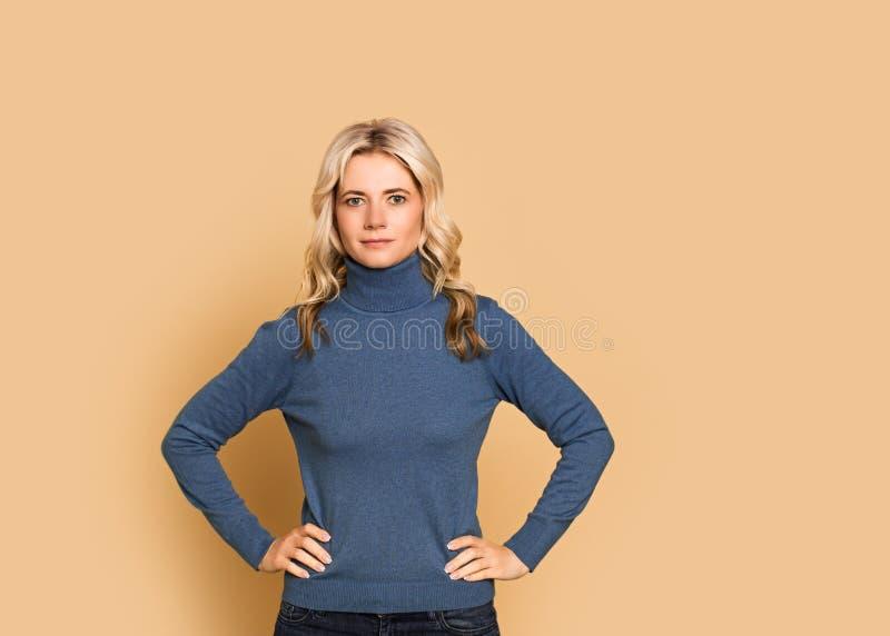 Ragazza cauasian e scandinava calma attraente adulta del fronte del ritratto della donna bionda bella, in maglione blu su fondo g fotografie stock