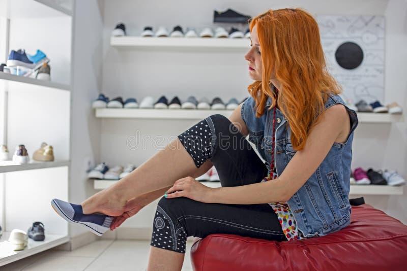 Ragazza caucasica della bella testarossa che sceglie e che indossa le nuove scarpe nel deposito fotografia stock