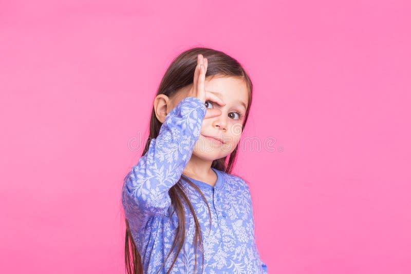 Ragazza caucasica sveglia che imbroglia intorno sul fondo rosa fotografia stock libera da diritti