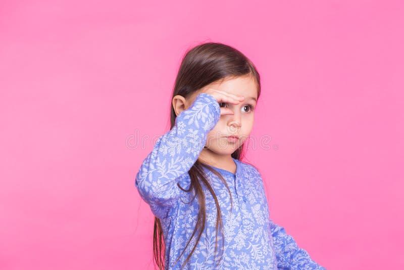 Ragazza caucasica sveglia che imbroglia intorno sul fondo rosa fotografia stock