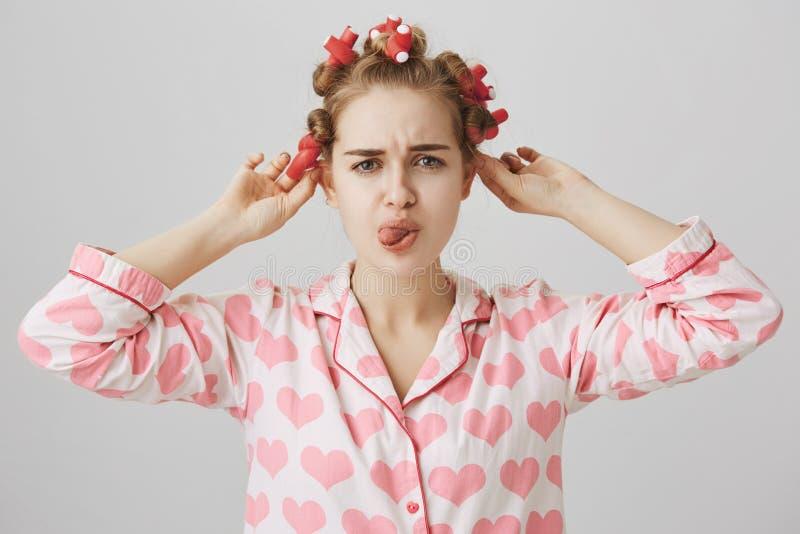 Ragazza caucasica sveglia importunata e messa a fuoco in capelli-bigodini, pigiami d'uso mentre in bagno, aggrottando le sopracci immagine stock