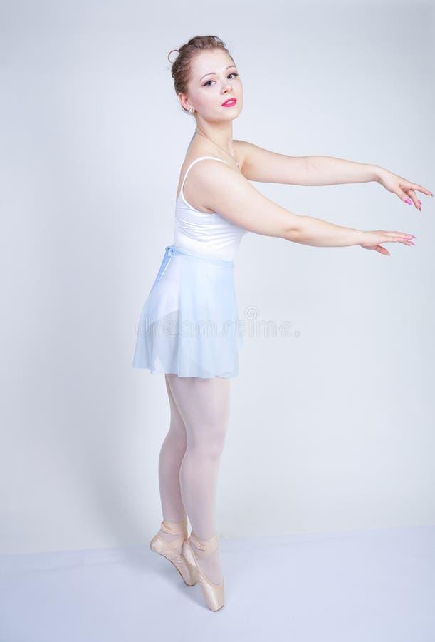 Ragazza caucasica sveglia in vestiti di balletto che impara essere una ballerina su un fondo bianco nello studio più i sogni dell fotografie stock libere da diritti