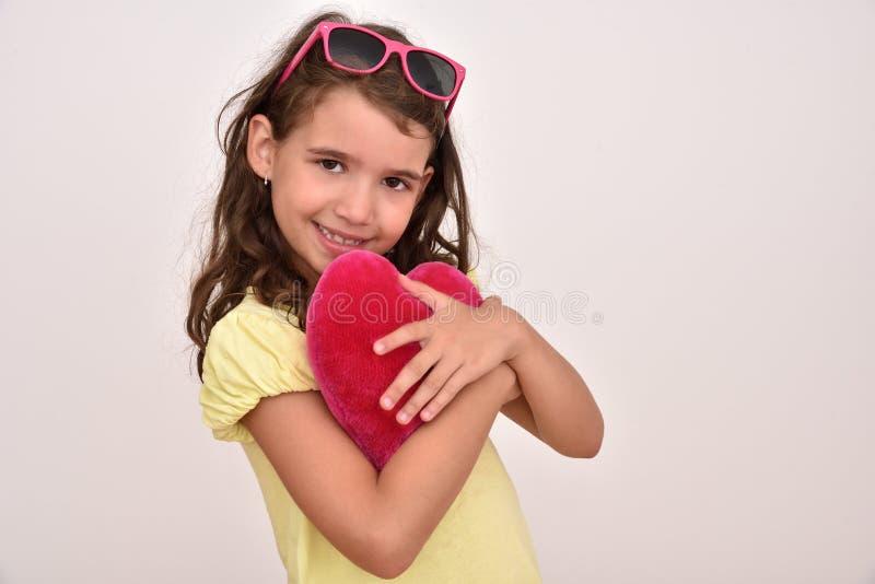 Ragazza che abbraccia il cuore di rosso della peluche fotografia stock