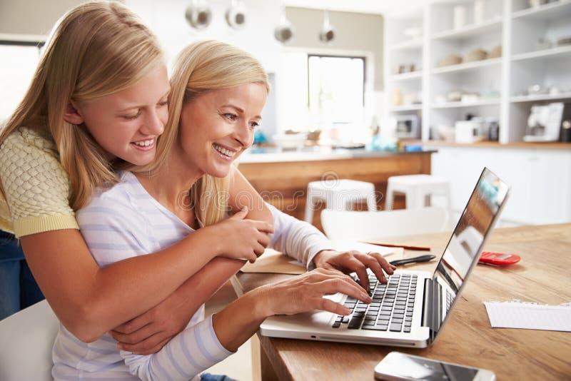 Ragazza che abbraccia sua madre, lavorante al computer portatile a casa immagini stock libere da diritti