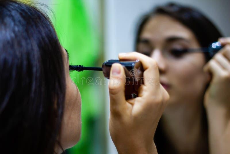 Ragazza che applica mascara nello specchio immagine stock libera da diritti