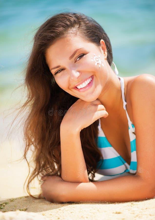 Ragazza che applica Sun Tan Cream immagini stock