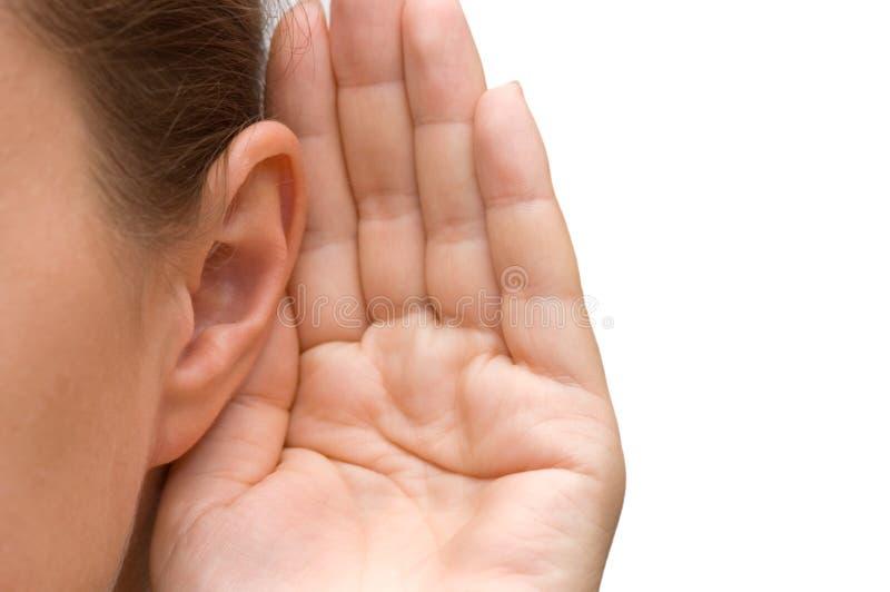 Ragazza che ascolta con la sua mano su un orecchio immagini stock libere da diritti