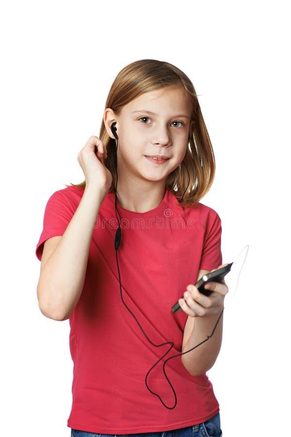 Ragazza che ascolta la musica sul vostro telefono immagine stock libera da diritti
