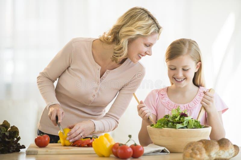 Ragazza che assiste madre nella preparazione dell'alimento al contatore fotografie stock