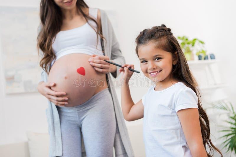 Ragazza che attinge pancia incinta della madre fotografia stock libera da diritti