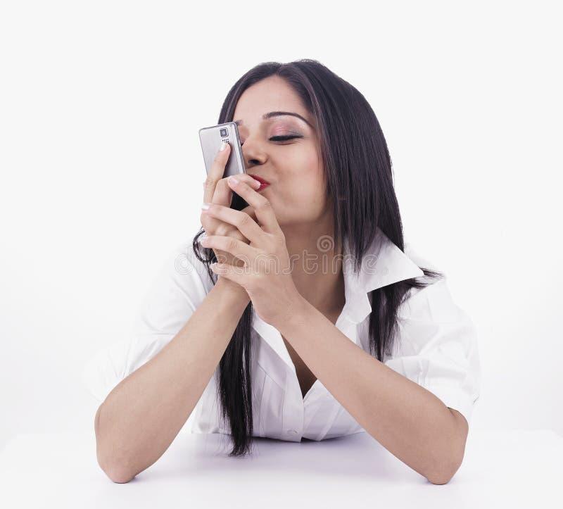 Ragazza che bacia il suo telefono delle cellule immagine stock