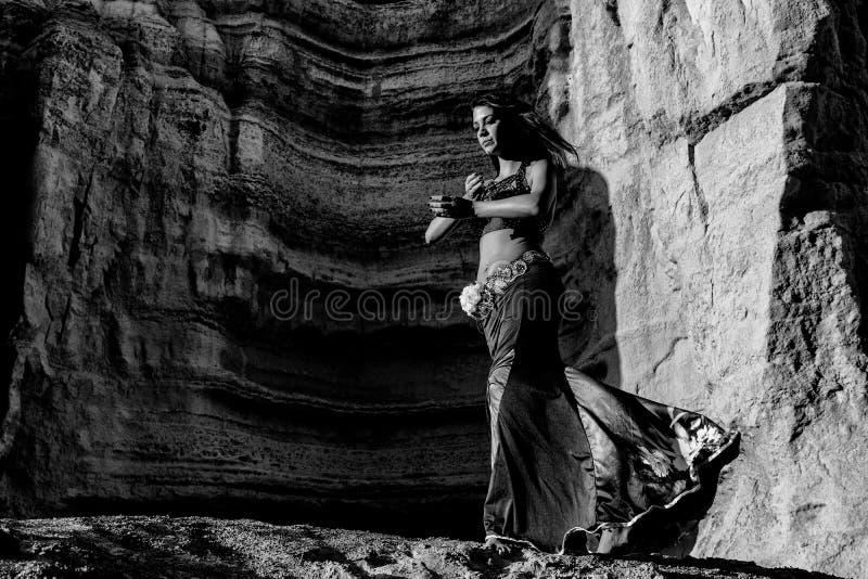 Ragazza che balla al ballo arabo famoso, danza del ventre con i canyon del deserto di Namibe nel fondo, ente e facciale estremi fotografia stock