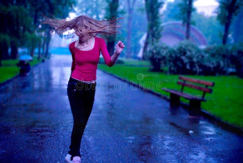 Ragazza che balla e che scuote i capelli sotto la pioggia fotografia stock