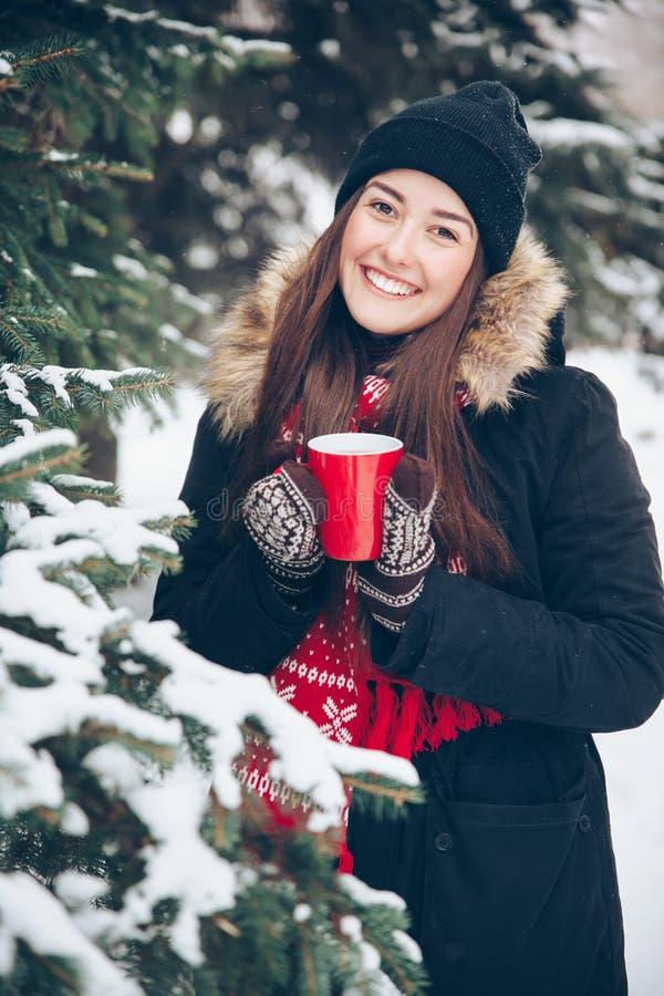 Ragazza che beve tè caldo nella foresta di inverno fotografie stock
