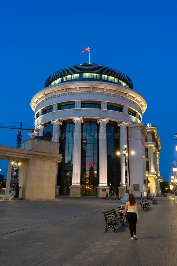Ragazza che cammina alla notte nelle vie di Skopje, Macedonia Costruzione e lampade illuminate di governo Monumenti storici in a immagine stock