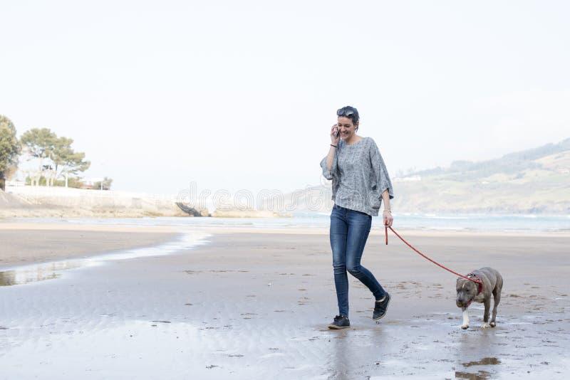Ragazza che cammina con il cane e che parla sul telefono. immagine stock
