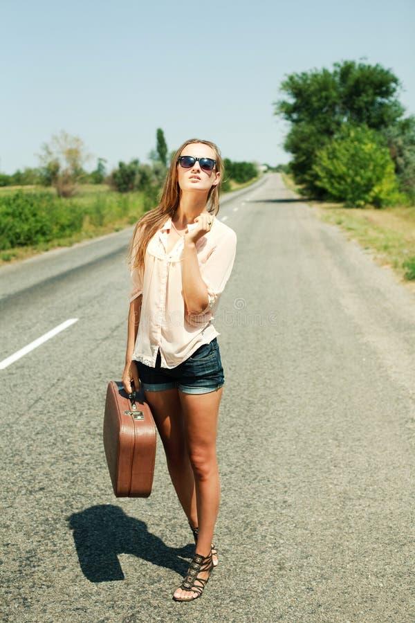 Ragazza che cammina con la valigia alla strada campestre immagini stock